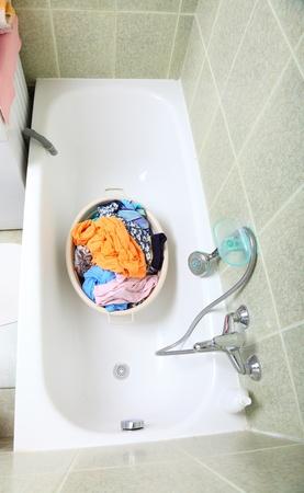 Pile of dirty laundry in bath washing machine green bathroom photo