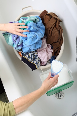 woman Pile of dirty laundry in bath washing machine green bathroom Stock Photo