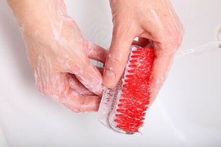 Woman wash red soapy hands in bathroom soap nail brush person scrubbing nails photo