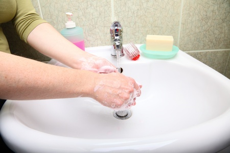 Woman wash red soapy hands in bathroom soap photo
