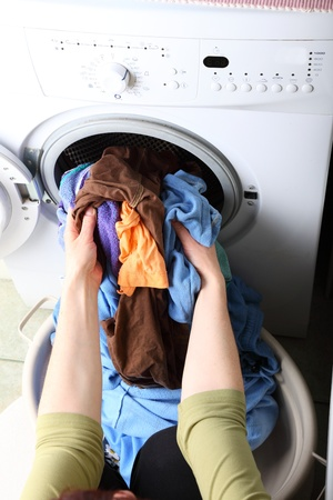 woman loading Preparation washing machine in bathroom clothes in the washing machine Stock Photo