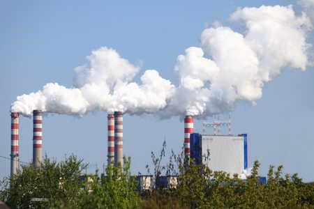 smoking chimneys from a power plant against a blue sky - Poland