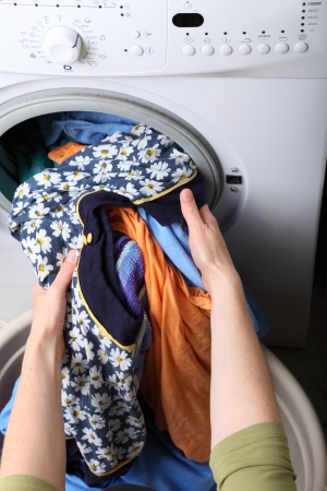overburden: woman loading Preparation washing machine in bathroom clothes in the washing machine Stock Photo