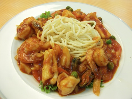 Spaghetti with tomato sauch and seafood on dish photo