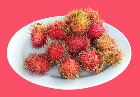 Rambutans on plate isolated on pink background Stock Photo - 9613115
