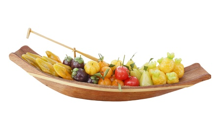 Isolated deletable imitation fruits arrangement in wood boat, Thai style dessert, inside coated with soy paste and jelly