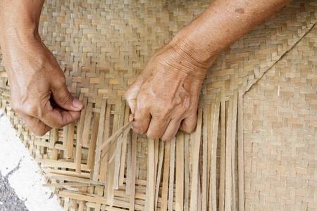 Thai woman hands weaving reed mat Stock Photo