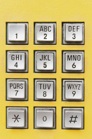 Buttons on yellow public telephone in Thailand