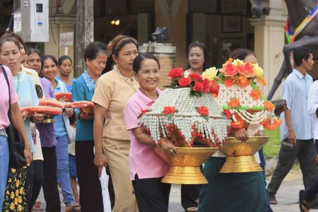 adulyadej: Nakhon Si Thammarat, Thailand - December 02, 2011 : Unidentified Thai women hold flower offering in parade of Celebration of candidate Buddhist novice during ordination ceremony to offer prayers for the King Bhumibol Adulyadej at Wat Srareang, Nakhon Si T Editorial