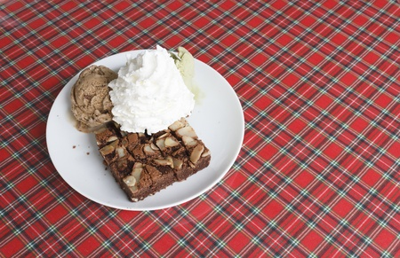 Piece of chocolate brownie with chocolate ice cream and green tea ice cream and whipped cream on plate photo