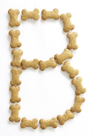 comida perro: Letra B hizo de los alimentos en forma de hueso de perro sobre fondo blanco, dispararon directamente desde arriba