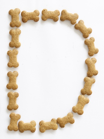 Letter D made of bone shaped dog food on white background, shot directly from above photo