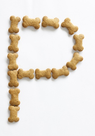Letter P made of bone shape dog food on white background, shot directly from above photo