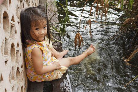 The playful girl sprays feet pond water Stock Photo - 12870754