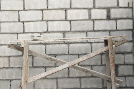 New building tan concrete block wall with scaffolding and braces photo