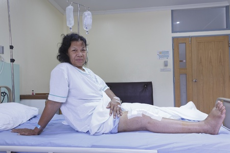 Knee replacement surgery after operation patient senior woman (60s) on the bed in hospital photo