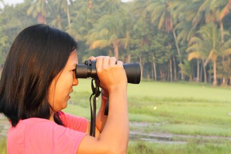 Thai woman looking the nature through binoculars photo