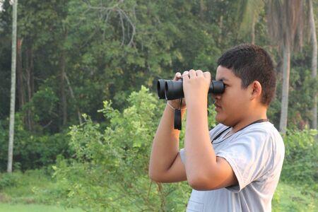 thai boy: Thai boy looking the nature through binoculars