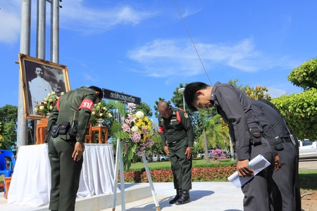 middleman: SURAT THANI, THAILAND - AUGUST 7 : Superintendent of the Amphoe Sawead Police Station lay wreath to the picture of Rapee Pattanasak on Rapee Day Prince Rapee Pattanasak, the father of Thailand on August 7, 2013 in Surat Thani, Thailand.