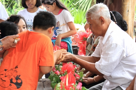 KRABI, THAILAND - APRIL 16  Unidentified Thai boy 10 years old celebrate Songkran  new year   water festival  by giving garlands to their seniors and asked for blessings on April 16, 2013 in Krabi, Thailand