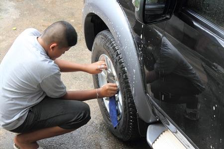 Thai boy washing a car photo
