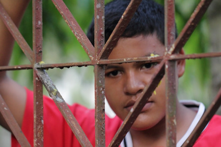 waiting convict: Portrait of Asian Thai boy behind an iron lattice
