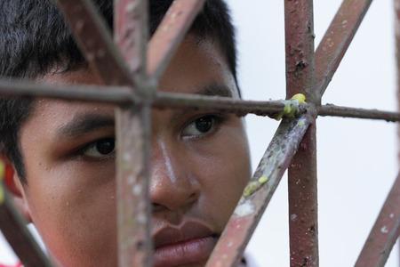 waiting convict: Portrait of Asian Thai boy behind an iron lattice