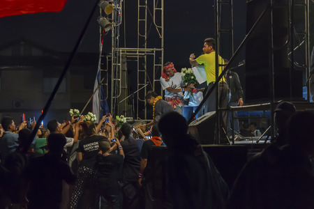 anti fascist: SURAT THANI, THAILAND - MARCH 3, 2014:Thai people give flowers to Dr.Jak Phanchupech before gives a speech during an anti-government rally on the protest stage at Chiya on March 3, 2014 in Surat Thani, Thailand. Editorial