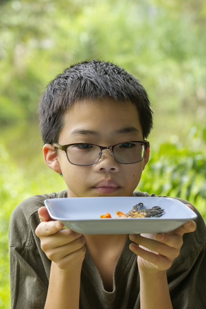 silver perch: Portrait of Asian Thai pensive boy looks at fish bone of white perch fish fried eaten clearly on plate