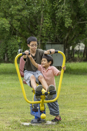 Happy Asian Thai boys playing together outside on playground photo