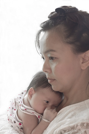 Asian Thai mother holding sweet little newborn baby boy