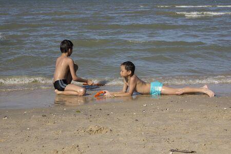 thai boy: Two Asian Thai boy play in the sand at the beach Stock Photo
