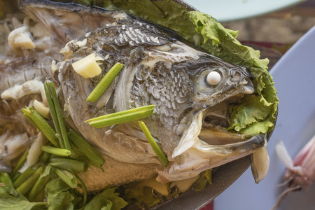 silver perch: Steamed white perch fish in lime dressing ingredient include garlic,ginger and light soy sauce Stock Photo