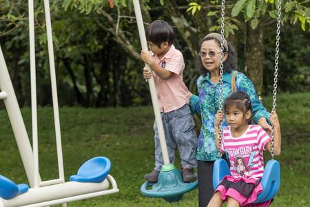 NAKHON SI THAMMARAT, THAILAND - OCTOBER 18: Asian Thai grandmother pushing kids on swing in playground on October 18, 2014 in Nakhon Si Thammarat province, Thailand.