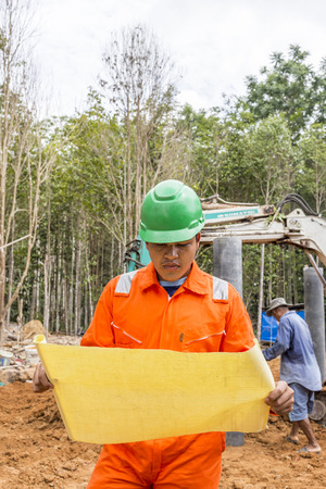 high visibility: NAKHON SRI THAMMARAT THAILAND  MAY 10: Thai construction site worker wearing high visibility safety jacket standing and watching paper on May 10 2015 in Nakhon Sri Thammarat Thailand.