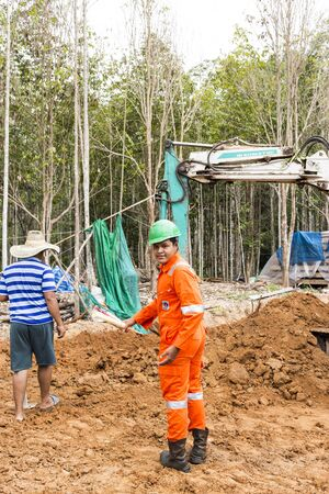 buildingsite: NAKHON SRI THAMMARAT THAILAND  MAY 10: Thai worker wearing high safety jacket standing and watching bucket digger digging at construction site on May 10 2015 in Nakhon Sri Thammarat Thailand. Editorial