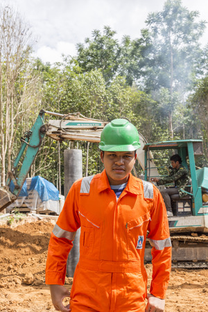 buildingsite: NAKHON SRI THAMMARAT THAILAND  MAY 10: Thai worker wearing high safety jacket with bucket digger digging at construction site on May 10 2015 in Nakhon Sri Thammarat Thailand. Editorial