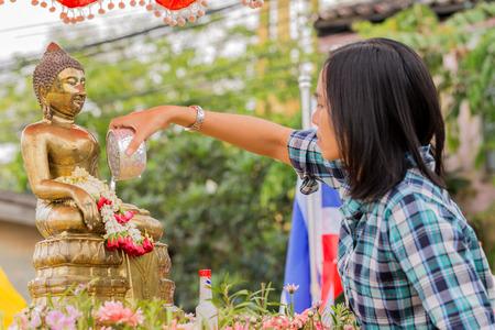 si: NAKHON SRI THAMMARAT, THAILAND - APRIL, 12: Unidentified Thai woman celebrate Songkran Festival by pouring water to Buddha statue on April 12, 2015 in Nakhon Si Thammarat, Thailand. Editorial