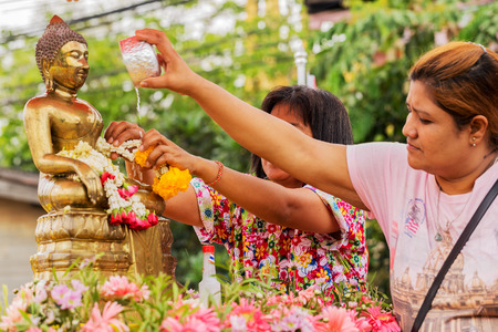 NAKHON SRI THAMMARAT, THAILAND - APRIL, 12: Unidentified Thai woman celebrate Songkran Festival by pouring water to Buddha statue on April 12, 2015 in Nakhon Si Thammarat, Thailand. Редакционное