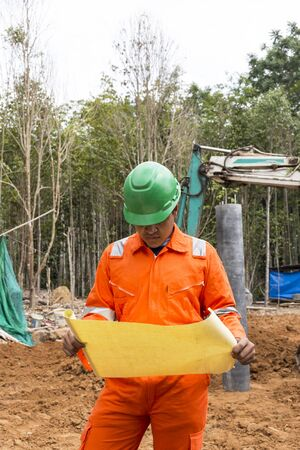 high visibility: Thai construction site worker wearing high visibility safety jacket standing and watching paper Stock Photo