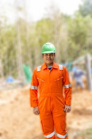 high visibility: Thai construction site worker wearing high visibility safety jacket standing