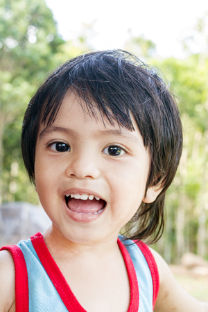 bebes lindos: Adorable happy Asian Thai young boy smiling for the camera