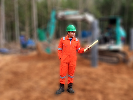 high visibility: Thai construction site worker wearing high visibility safety jacket standing and hold paper Stock Photo