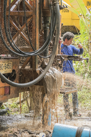 construction crew: NAKHON SI THAMMARAT, THAILAND - DECEMBER 7: Man working a drilling rig to a water well for crop irrigation on December 7, 2015 in Nakhon Si Thammarat, Thailand.
