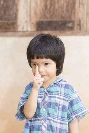 gesturing: Asian little child boy gesturing exclamation point finger sign Stock Photo