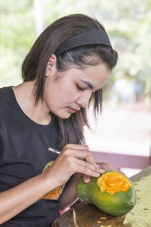 papaya flower: Asian Thai woman carving papaya