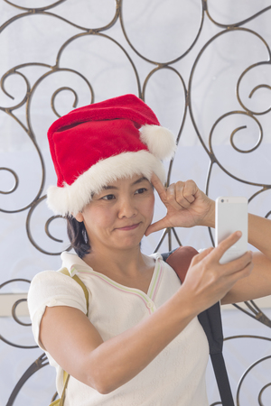 sexy pictures: Asian Thai woman in santa hat taking picture selfie by smatrphone