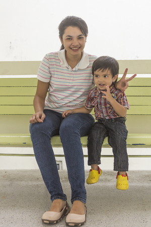 mother on bench: Asian Thai little boy sitting on bench his mother