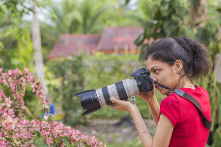asian gardening: Asian Thai young woman photographer with dslr camera take a picture in flowers gardening and blurred background