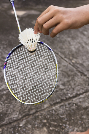 serve: Hand of badminton player with racket and shuttlecock serve